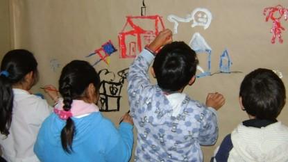 niños dibujando pared